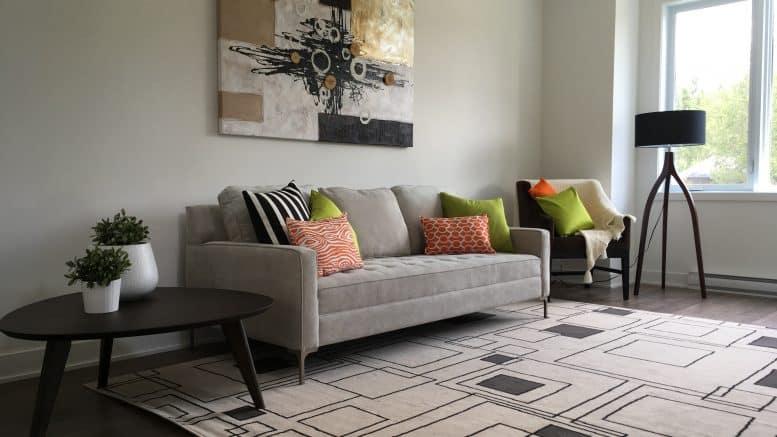 Sofa au centre d'une table à café et d'un fauteuil dans le salon d'une habitation du Carrefour de l'Auberge, des locations résidentielles à Orford.