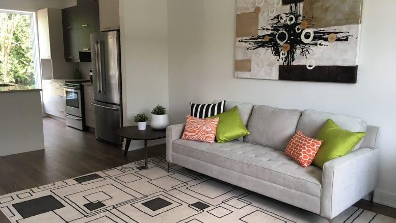 Sofa et table à café dans le salon et cuisine à l'arrière d'une résidence du projet de Carrefour de l'Auberge à Orford.